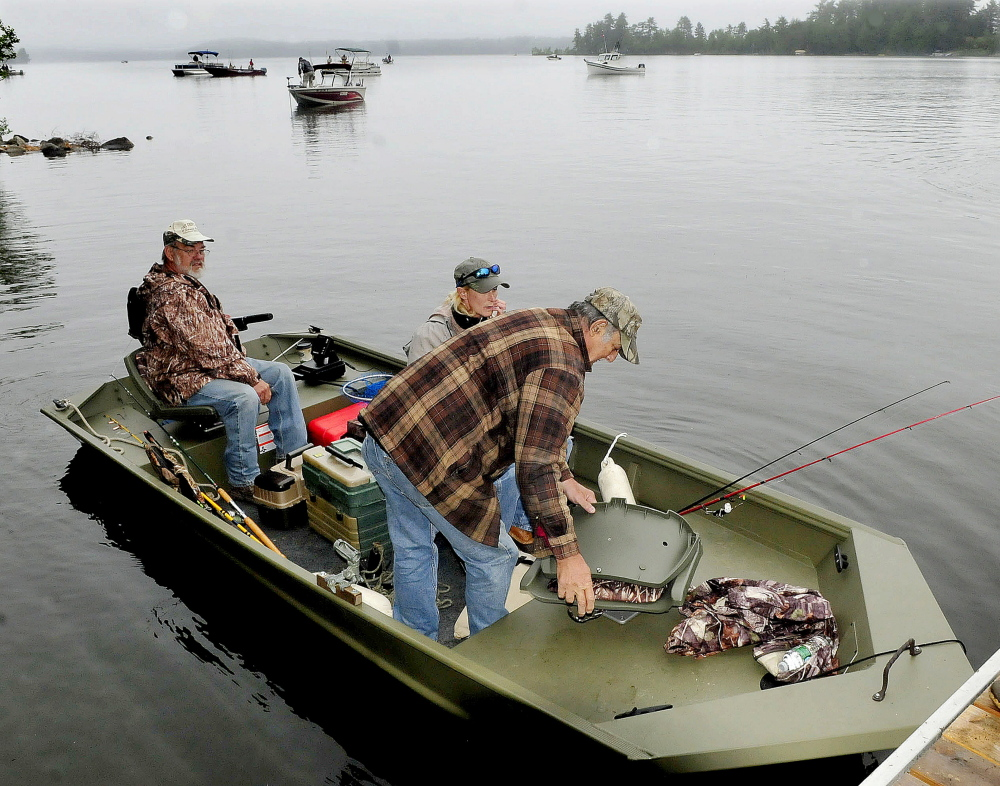 Veteran Frank Evangelista, of Solon, right, gets into a fishing boat Tuesday with his daughter, Lori Geib, of Carrabassett Valley, to fish on Great Pond in Belgrade as part of the Fishing Extravaganza for area veterans while volunteer boat operator Terry Huffman backs away.