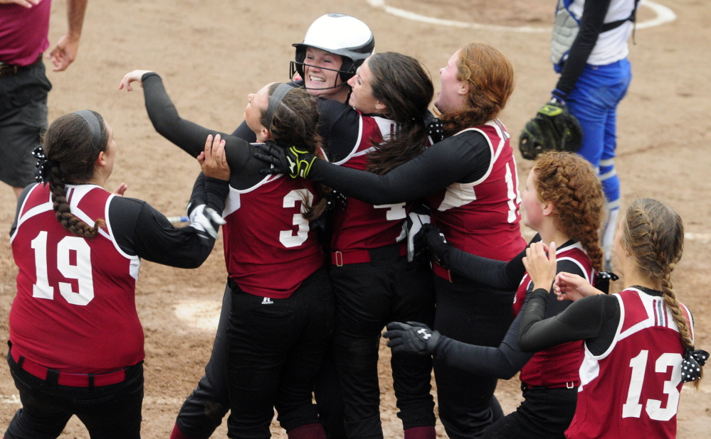 Staff photo by Joe Phelan   Members of the Richmond softball team mob Kelsea Anair (wearing helmet) after she scored the team's 12th and final run to end the Western D title game against Searsport on Tuesday at St Joseph's College. Kelsie Obie delivered the game-winning hit in the fifth inning for Richmond, which prevailed 12-0 to win its sixth consecutive regional crown.