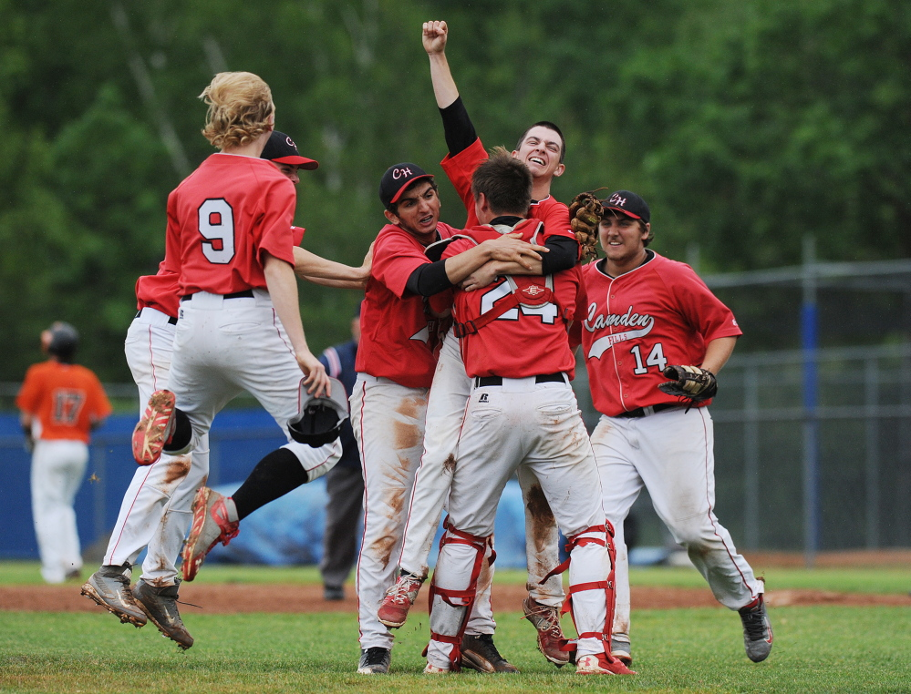 Members of the Camden Hills baseball team celebrate their 3-1 victory over Winslow in the Eastern B title game Tuesday at Mansfield stadium in Bangor. The Windjammers won 3-1.