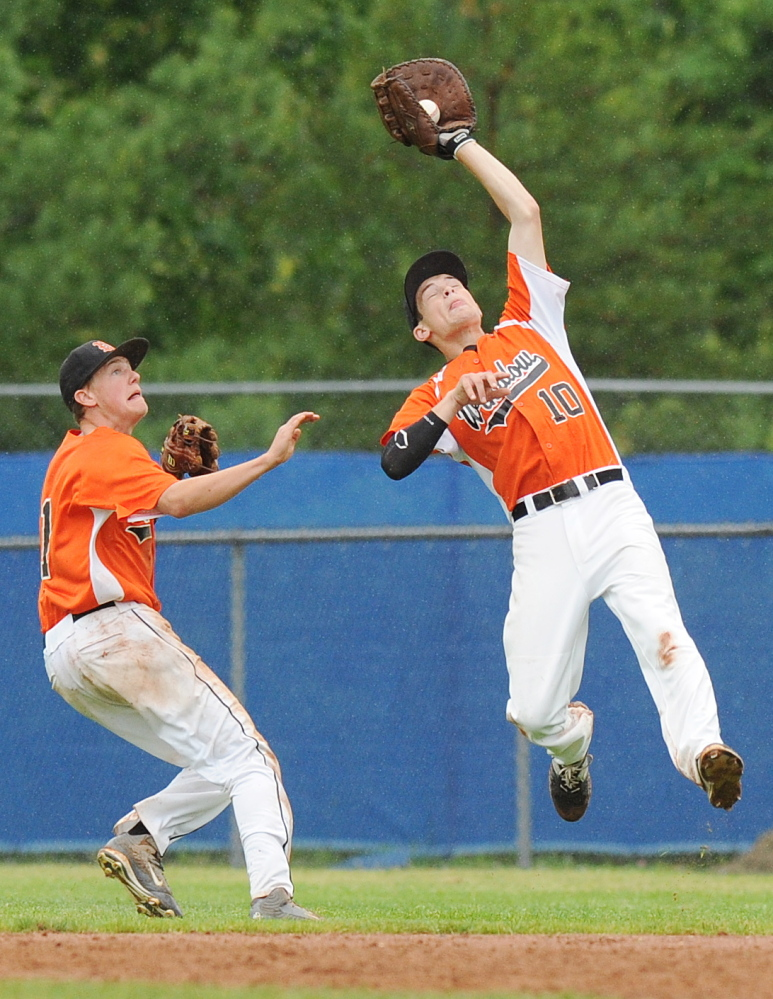 Winslow's Jon Nerney, right, makes the catch in right field as Jacob Trask backs him up during the seventh inning of the Eastern B title game Tuesday in Bangor.