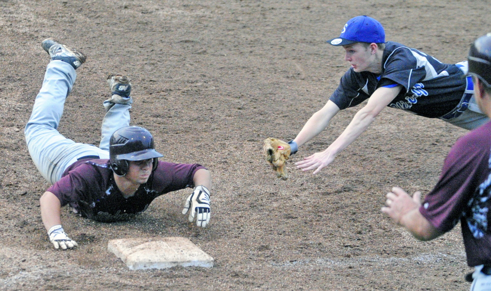 Richmond baserunner Curtis Anderson dives back to first before Searsport first baseman Liam MacMIllan can apply the tag during the Western D title game Tuesday at Larry Mahaney Diamond at St. Joseph's College in Standish.
