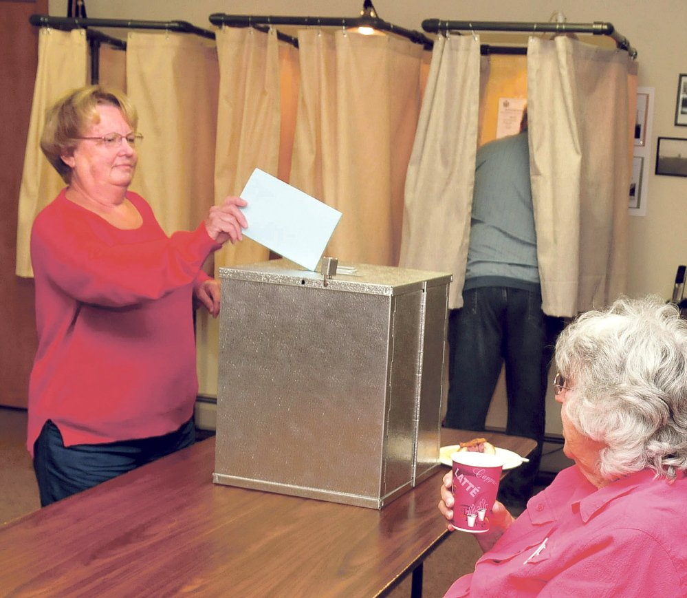 Benton resident Patricia Evers casts her School Administrative District 49 school budget ballot as her husband, Jim, fills out his and clerk Karleen Proctor monitors voting on Tuesday in Benton.