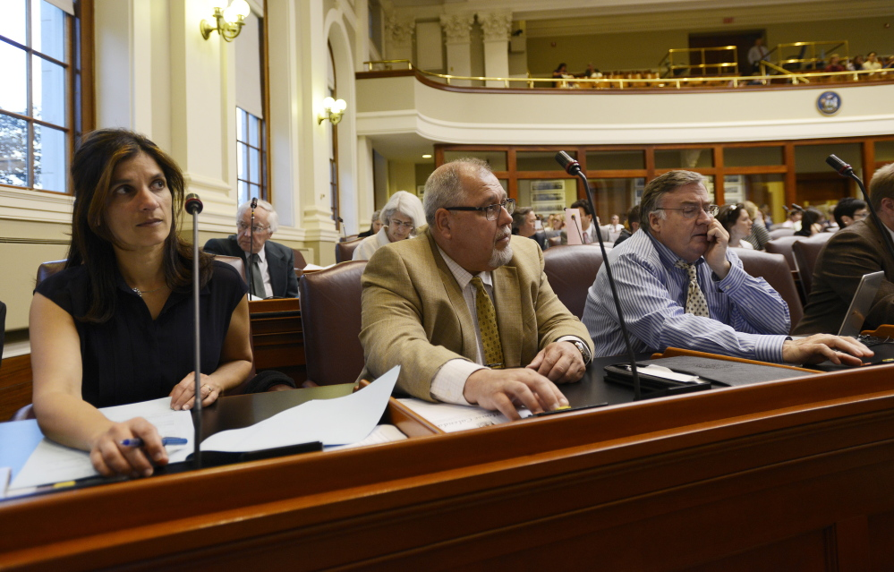 Left to right, Representatives Sara Gideon of Freeport, Mark Dion of Portland and Chuck Kruger of Thomaston cast a vote during a house session to take override votes Thursday, June 18, 2015. (Photo by Shawn Patrick Ouellette/Staff Photographer)