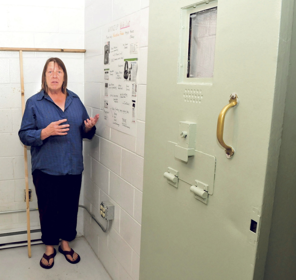 Lolly Phoenix speaks about radio station needs Tuesday inside the WXNZ-LP studio in the former Somerset County Jail in Skowhegan. At right is a sliding reinforced jail door in a cellblock.