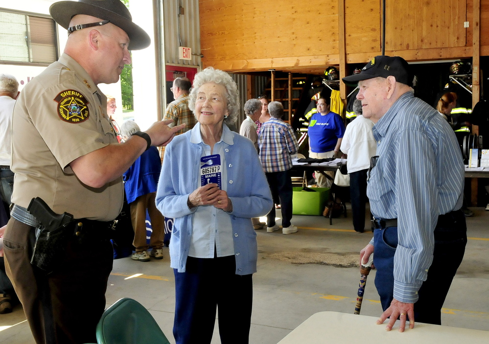 Franklin County Sheriff Scott Nichols speaks with Gloria and Lincoln Grush, of Jay, on Thursday during the Senior Resource Fair at Wilton's Public Safety Building.