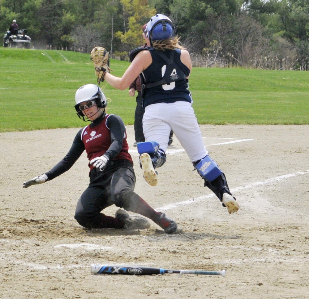 Richmond's Sydney Tilton, bottom, slides safely into home plate by Greenville catcher Lindsay Fenn during a game May 9 in Richmond.