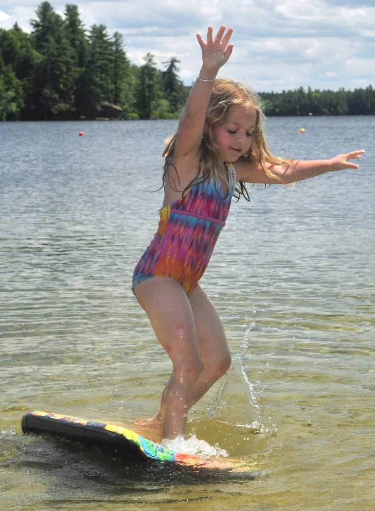 Shae LePage tries out her boogie board Friday in Maranacook Lake at the Readfield Town Beach in Readfield.