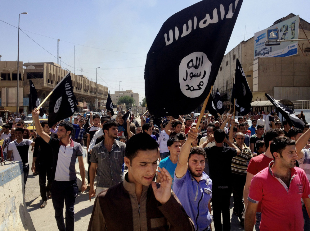 In this Monday, June 16, 2014 file photo, demonstrators chant pro-Islamic State group slogans as they wave the group's flags in front of the provincial government headquarters in Mosul, 225 miles (360 kilometers) northwest of Baghdad, Iraq. )