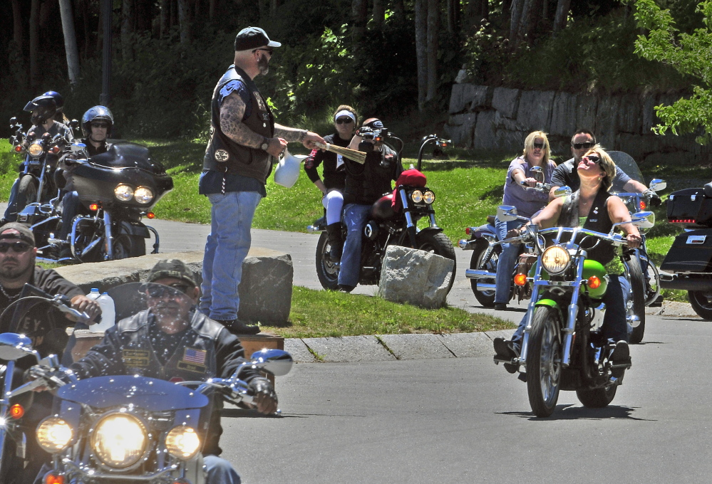 The Rev. Tony Balcer sprinkles water onto passing motorcyclists as they start a ride Saturday during the Blessing of the Bikes event, which was part of the Greater Gardiner River Festival.
