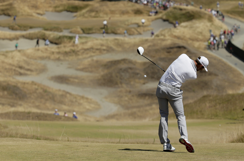 Dustin Johnson hits his tee shot on the fourth hole during the final round of the U.S. Open golf tournament at Chambers Bay on Sunday, June 21, 2015 in University Place, Wash.