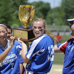 Messalonskee  team captains Mollyan Killingbeck, left, and Kristy Prelgovisk, who hit a home run in the first inning  for the only score of the game, get the trophy from their coach, Leo Bouchard after Messalonskee beat Scarborough in the Class A state championship game Saturday in Augusta.