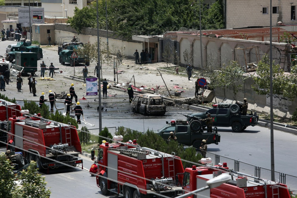 Afghan security forces and first responders  gather at the site of a complex attack by Taliban fighters in front of the Parliament, in Kabul, Afghanistan, Monday.