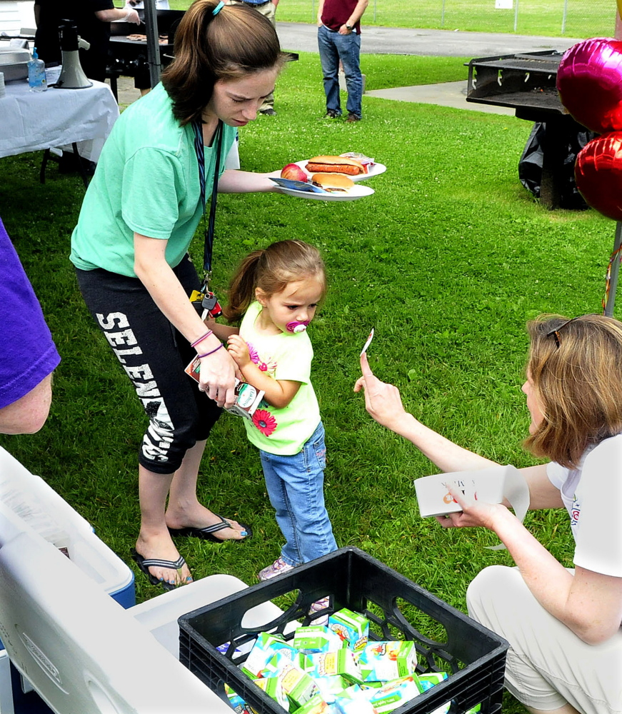 Katie Hoffman of the Maine Dairy and Nutrition Council offers a sticker to McKenzie Reynolds and her mother, Nikida, during the Waterville kickoff of the AOS 92 and USDA summer food program on Monday.