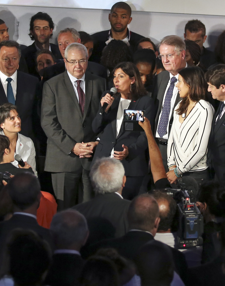 Paris mayor Anne Hidalgo, center, announces the candidacy of Paris for the 2024 Olympic games, in Paris, Tuesday.