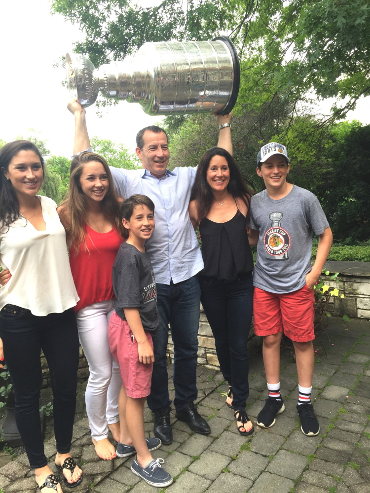 Former Portland Pirates coach Kevin Dineen and his family, from left, Hannah, Emma, Declan, Kevin, Annie and William, share a moment with the Stanley Cup in the backyard of Chicago head coach Joel Quenneville last week in Hinsdale, Illinois.
