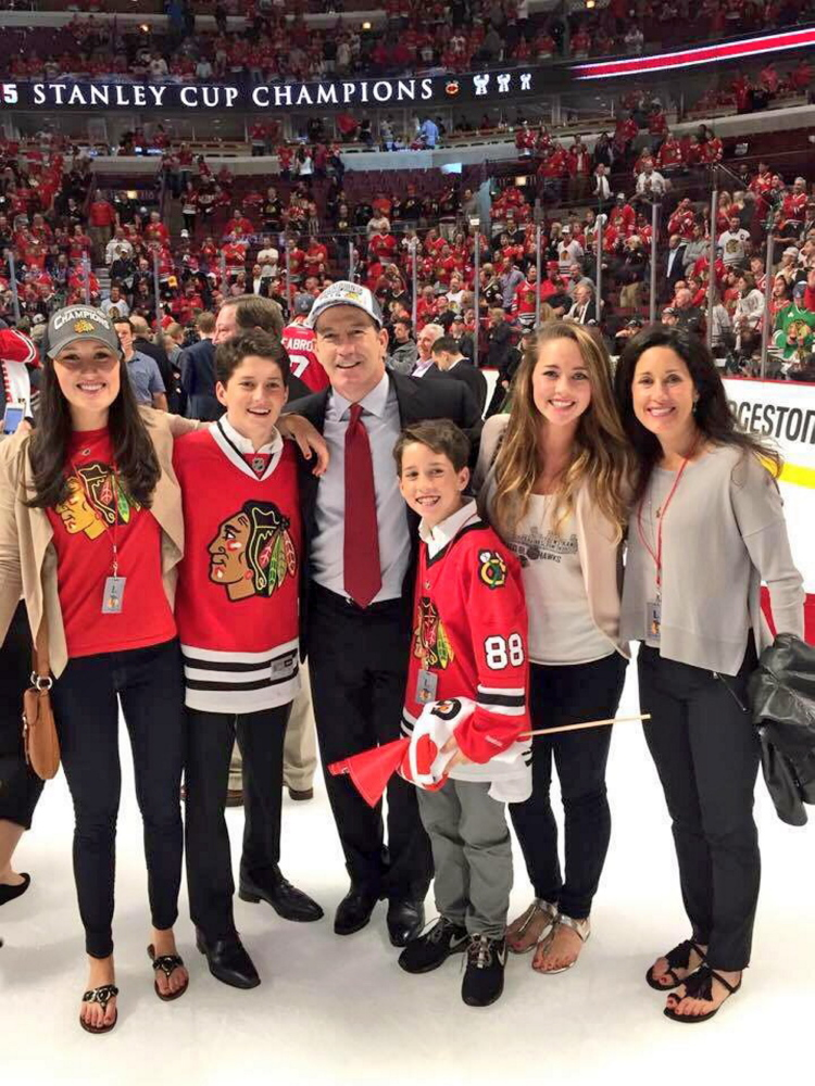 Former Portland Pirates coach Kevin Dineen and his family, from left, Hannah, William, Kevin, Declan, Emma and Annie, celebrate the Blackhawks clinching victory on the United Center ice earlier this month.