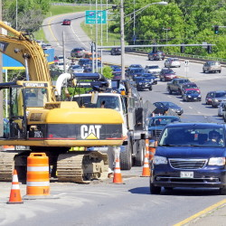 Westbound traffic on Western Avenue narrows to a single lane on Wednesday as drivers go around a crew repairing a water main break near the Homewood Suites motel construction site.