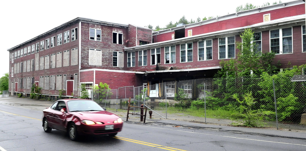 A motorist passes by the Forster Mill on Tuesday in Wilton. The town took over the mill through foreclosure last spring and is slowly moving toward demolition, helped by $25,000 approved at Town Meeting last week.
