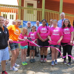 Along with the YMCA staff and community leaders, Olympian Julia Clukey helps campers Talia Nussinowl, Gabby Sienko, Fifi Mathieu, Cali Berhar and Lucy Pruett cut the ribbon at the ceremony on Wednesday, June 17, at Julia Clukey's Camp for Girls at Camp KV in Readfield.
