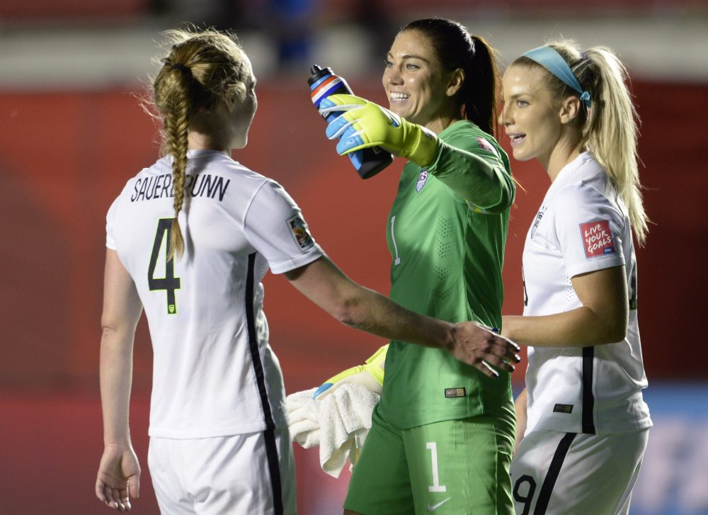 U.S. goalie Hope Solo and teammates Julie Johnston (19) and Becky Sauerbrunn (4) celebrate the team's win over China in a quarterfinal match Friday in the FIFA Women's World Cup in Ottawa, Ontario, Canada.