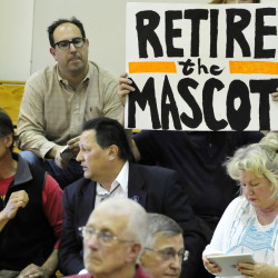 Mark Roman holds a sign calling for the retirement of the Indians nickname for Skowhegan area school sports teams during a forum on May 4. At far left is the former chief of the Penobscot tribe, Barry Dana, of Solon.
