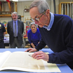 Sam Webber looks at the writing on the back of the city's 1776 copy of the Declaration of Independence in this April file photo taken at the Maine State Museum in Augusta.