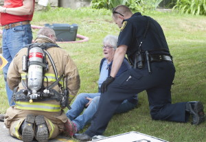 Battalion Chief David Groder of the Augusta Fire Department, left, and Augusta patrolman Brad Chase attend to Rebecca Poulin as she watches firemen put out a fire in the kitchen of her home at 65 School St. in Augusta on Monday.