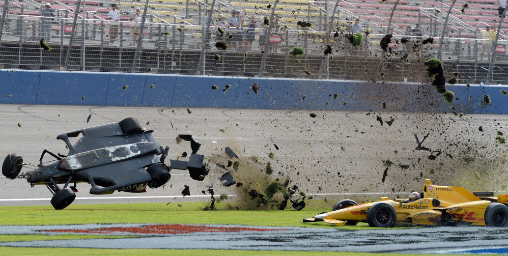 AP photo   Ryan Briscoe flips through the infield grass in front of Ryan Hunter-Reay on Saturday  during the IndyCar auto race at Auto Club Speedway in Fontana, Calif.