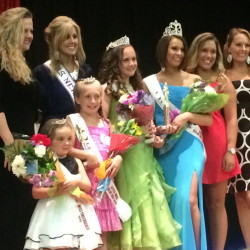 The winners of the Winslow Miss 4th of July pageant on stage Saturday, including Miss 4th of July Molly Lybrook, wearing the blue dress. It was later found that votes were tallied incorrectly and Lybrook didn't win. Organizers want Lybrook and the new winner, Caitlin Grenier, to share the crown, but Lybrook doesn't want to.