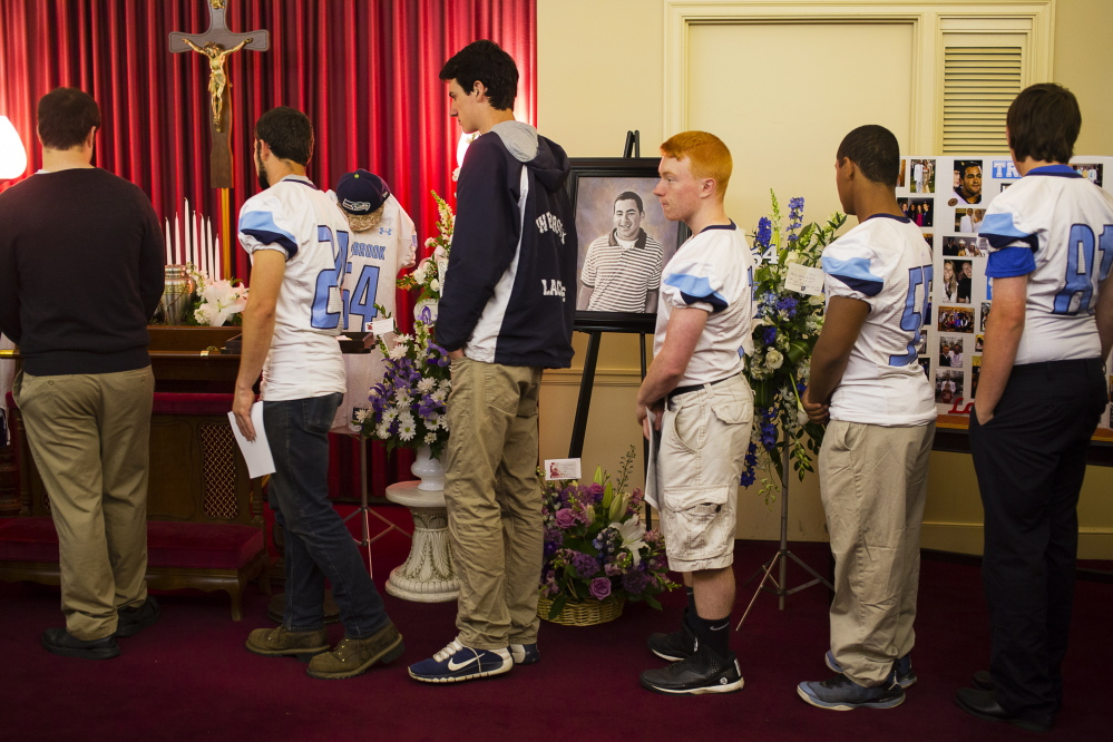 Westbrook High School athletes pay their respects to Treyjon Arsenault, a WHS alumnus and former football team captain, during his wake at the Jones, Rich and Hutchins Funeral Home in Portland on Sunday.