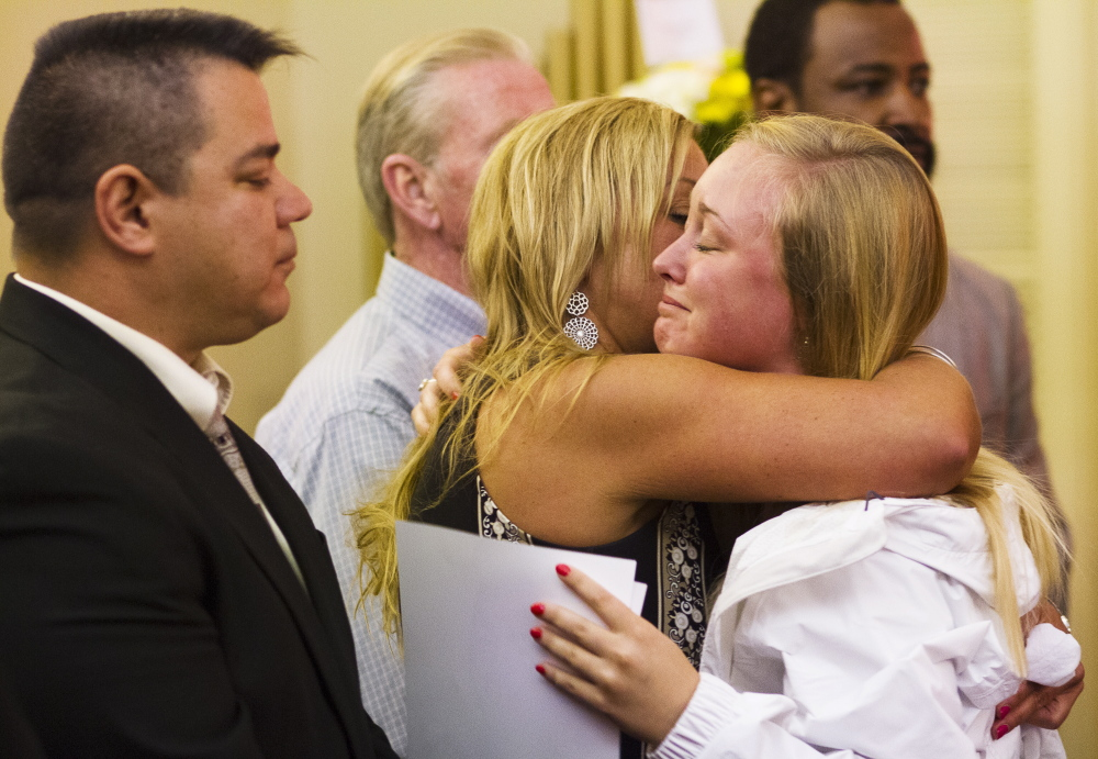 Nancy Laxson, mother of Treyjon Arsenault, embraces one of her son's friends Abby LeBlanc, 20, of Westbrook, at Treyjon's wake. Treyjon's stepfather, Donald Laxson, left, and Treyjon's  father, Turhan Walker, right, are in the receiving line.