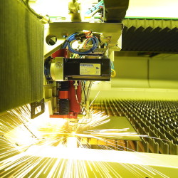 A computer-controlled laser machine cuts a metal plate during the fine-tuning of equipment being installed at Modula storage products in Lewiston. Once the installation is done, the company will need more workers.