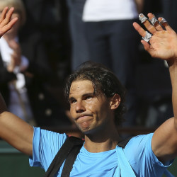 Spain's Rafael Nadal waves goodbye to spectators as he leaves center court while Serbia's Novak Djokovic celebrates winning the quarterfinal match of the French Open tennis tournament in three sets, 7-5, 6-3, 6-1, at the Roland Garros stadium, in Paris, France, on Wednesday.