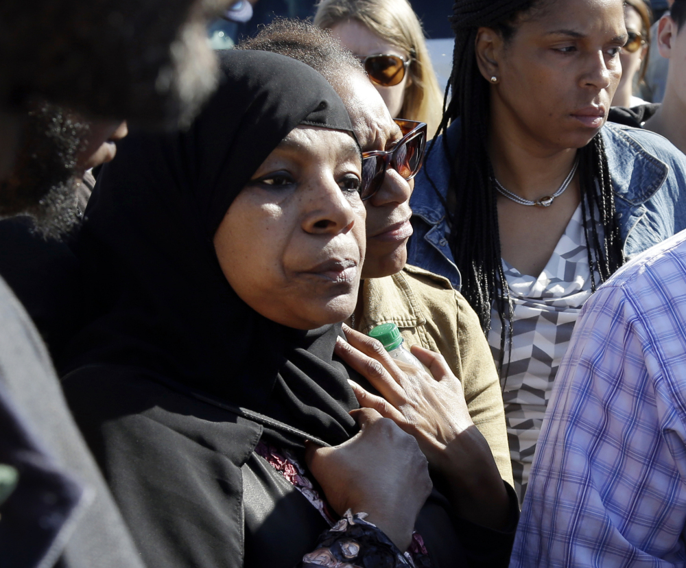 Rahimah Rahim, left, mother of shooting victim Usaama Rahim, listens during a news conference Thursday in Boston's Roslindale neighborhood in the area where Rahim was shot to death.