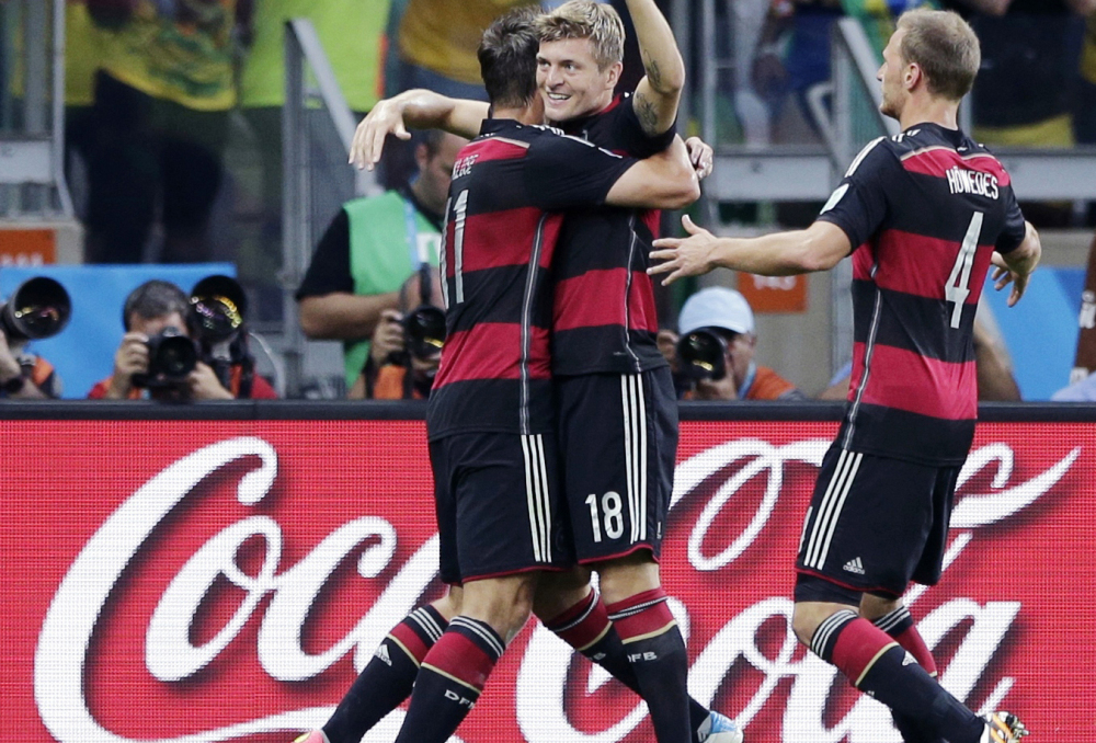 Germany's Toni Kroos, center, celebrates near a Coca-Cola advertisement after scoring a goal during the 2014 World Cup semifinal soccer match between Brazil and Germany.