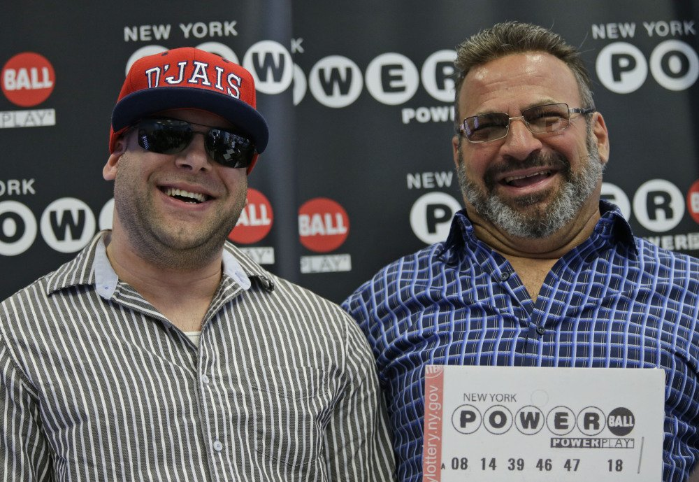 Anthony Perosi, right, holds a copy of the winning Powerball ticket with his son, Anthony Perosi III, in New York on Thursday.