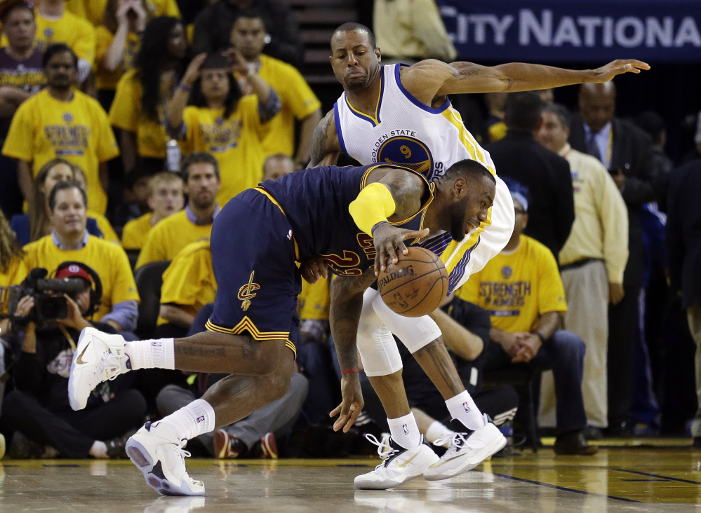LeBron James drives against Golden State Warriors forward Andre Iguodala during overtime Thursday night. The Cavaliers scored just two points in the overtime and dropped Game 1.