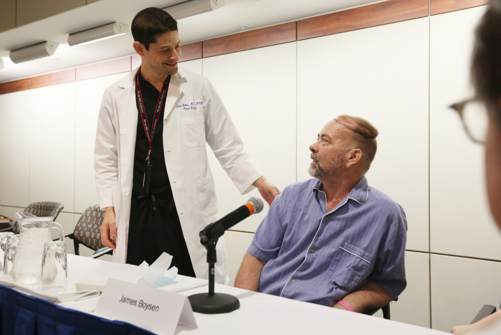 """Jim Boysen, right, received a partial skull and scalp transplant to treat a large head wound that he had developed as a result of cancer treatment. """"I'm still ... in awe of it,"""" he said."""