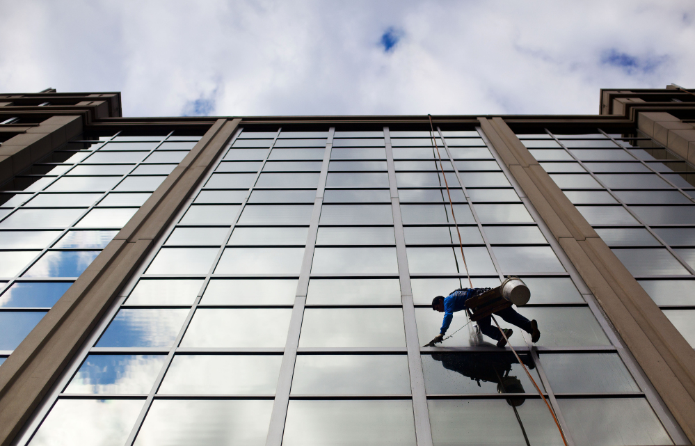 A window washer cleans the windows of an office building in downtown Washington. Friday's solid jobs report confirms the economy's vitality.
