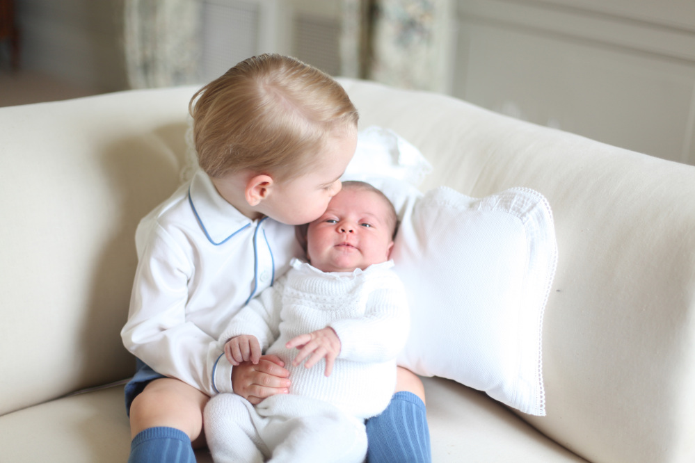 This image made available by Kensington Palace Saturday, June 6, 2015, taken by Kate, Duchess of Cambridge, at Amner Hall, eastern England in mid-May 2015 shows Britain's Princess Charlotte, right, being held by her brother, 2-year-old, Prince George. Duchess of Cambridge/ The Associated Press