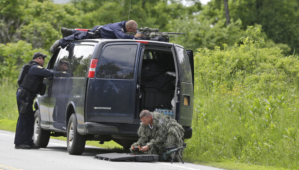 A law enforcement agent looks through a sniper scope while another in camouflage assembles a weapon during a search for two escaped killers in Boquet, N.Y., Tuesday.