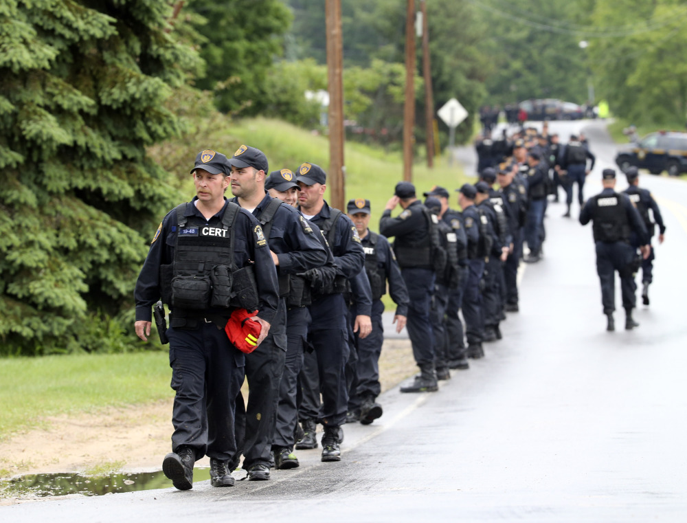 Law enforcement officers walk along Trudeau Road at Route 3 after emerging from the woods during a search for two escapees from Clinton Correctional Facility on Friday, June 12, 2015, near Dannemora, N.Y. Squads of law enforcement officers are searching for David Sweat and Richard Matt, two murderers who escaped from the maximum-security prison in northern New York. (AP Photo/Mike Groll)