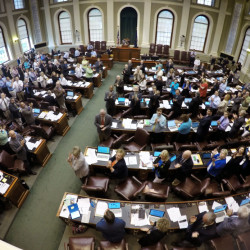 Members of the Maine House stand to acknowledge guests in attendance during a legislative session at the State House, Tuesday, June 16, 2015, in Augusta, Maine. Lawmakers have announced a budget agreement that they say will prevent a shutdown of state government. Democratic and Republican legislative leaders announced the bipartisan agreement late Monday night that includes tax cuts, investment in students and workers, property tax relief and welfare reform. (AP Photo/Robert F. Bukaty)