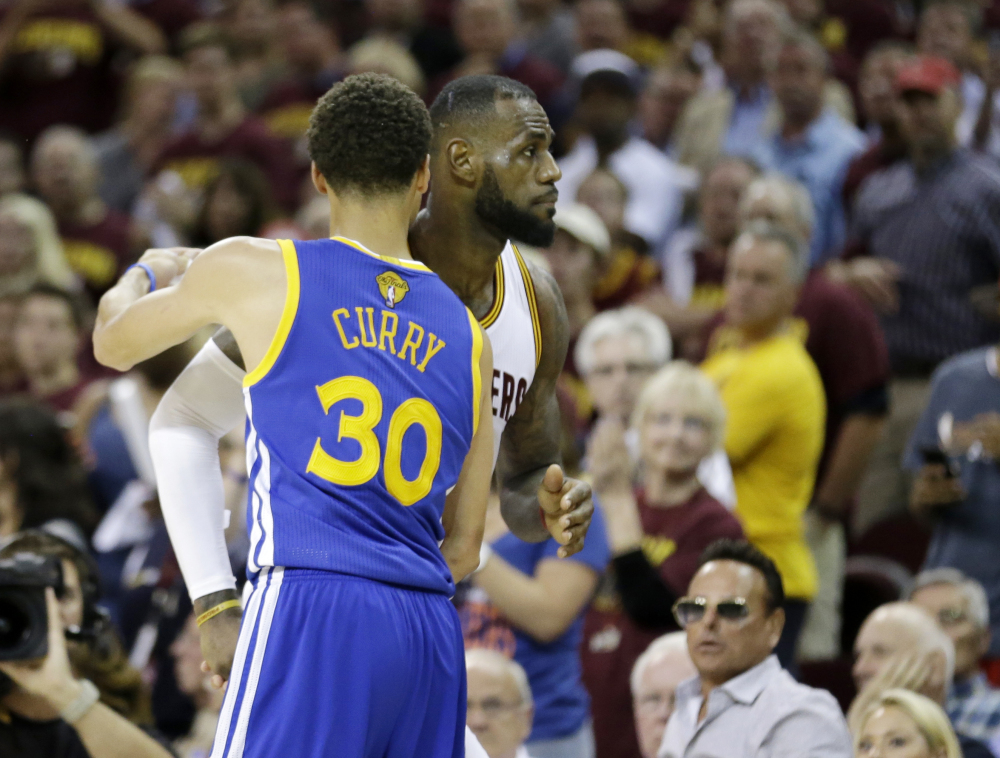 Warriors guard Stephen Curry hugs LeBron James as Game 6 winds down Tuesday night in Cleveland. The Warriors defeated the shorthanded Cavaliers, 105-97, to win the best-of-seven game series 4-2.