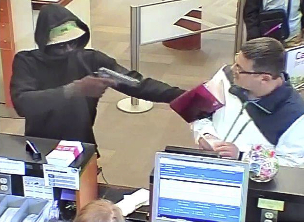 A robber points a gun at a man during the robbery of the Bank of America branch at One City Center in Portland on Friday in this image from a bank security camera.