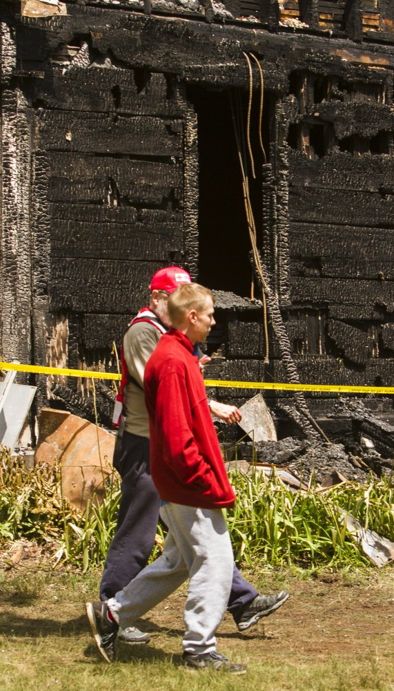 Jonathan Cressey, a resident of the charred house at 305 Cat Mousam Rd. in Kennebunk, walks past the structure with a Red Cross volunteer Monday. Authorities say Cressey climbed from a second-story window and saved his father on the first floor, but couldn't get to his brother, who died in the blaze early Monday morning.