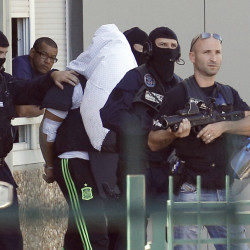 The suspect in the beheading of a businessman, Yassine Salhi, a towel over his head to mask his face, is escorted by police officers as they leave his home in Saint-Priest, outside the city of Lyon, central France, Sunday.