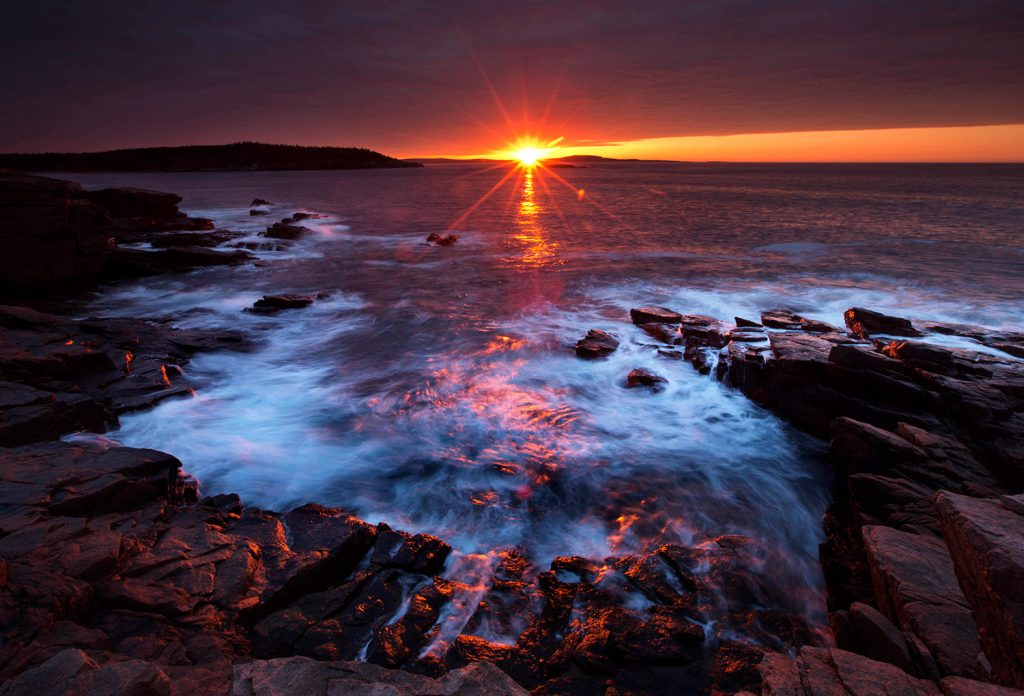 The sun's rays strike the rocky coast of Acadia National Park, Maine. The Associated Press