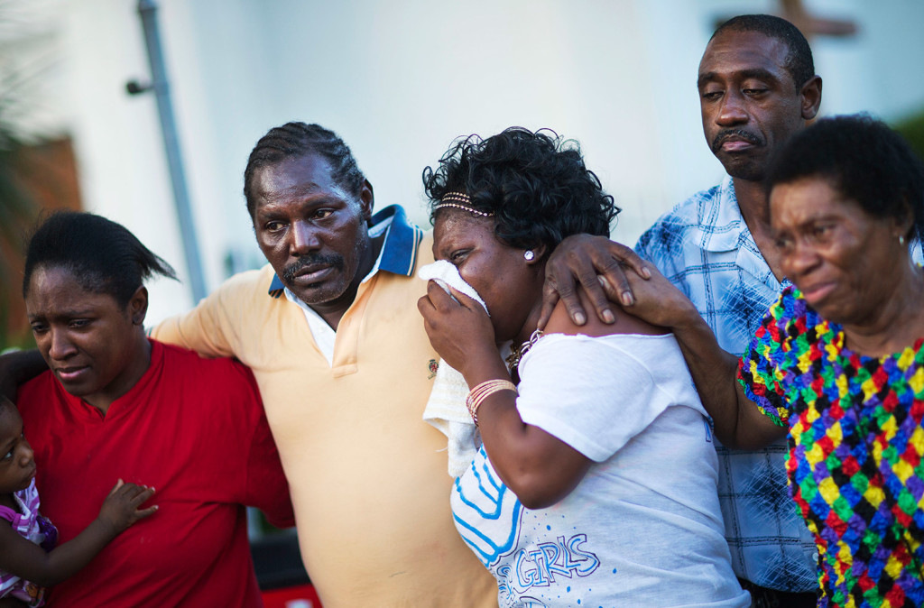 Gary and Aurelia Washington, center left and right, the son and granddaughter of Ethel Lance who died in Wednesday's shooting, leave a sidewalk memorial in front of Emanuel AME Church comforted by fellow family members.