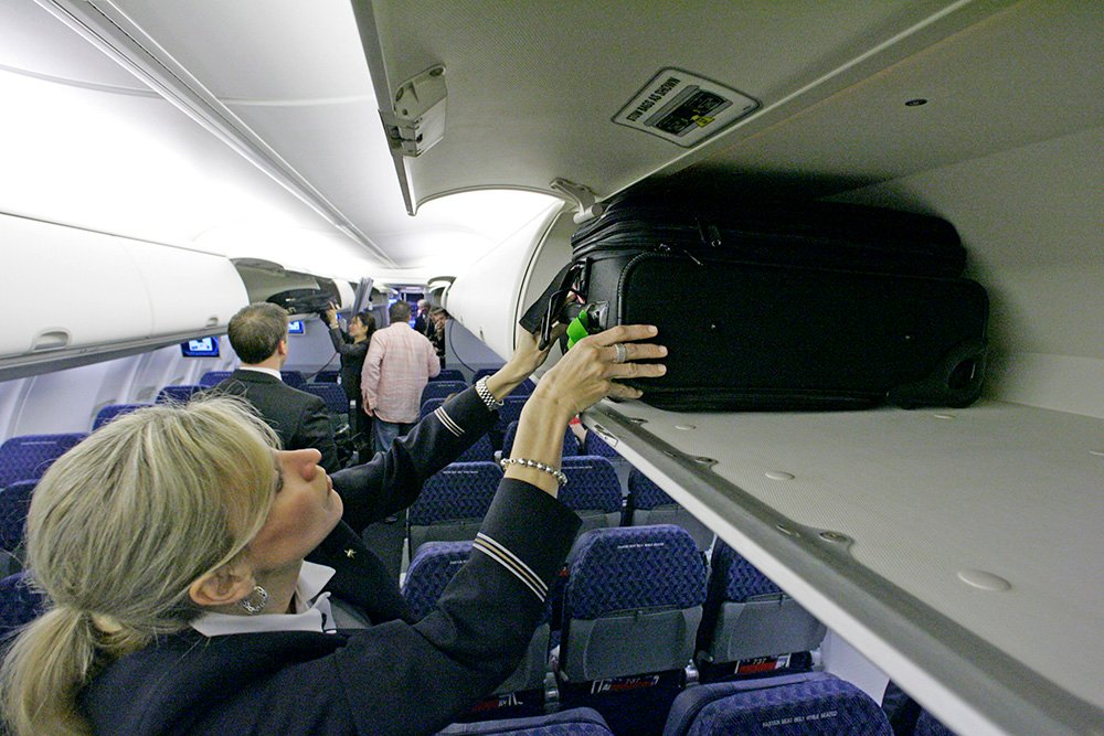 An American Airlines flight attendant loads a bag in the overhead bin of  a Boeing 737-800 jet, at Dallas Fort Worth International Airport in Grapevine, Texas. The Associated Press